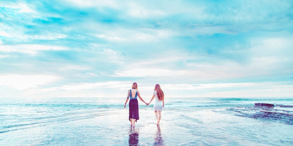 two women holding hands on the beach