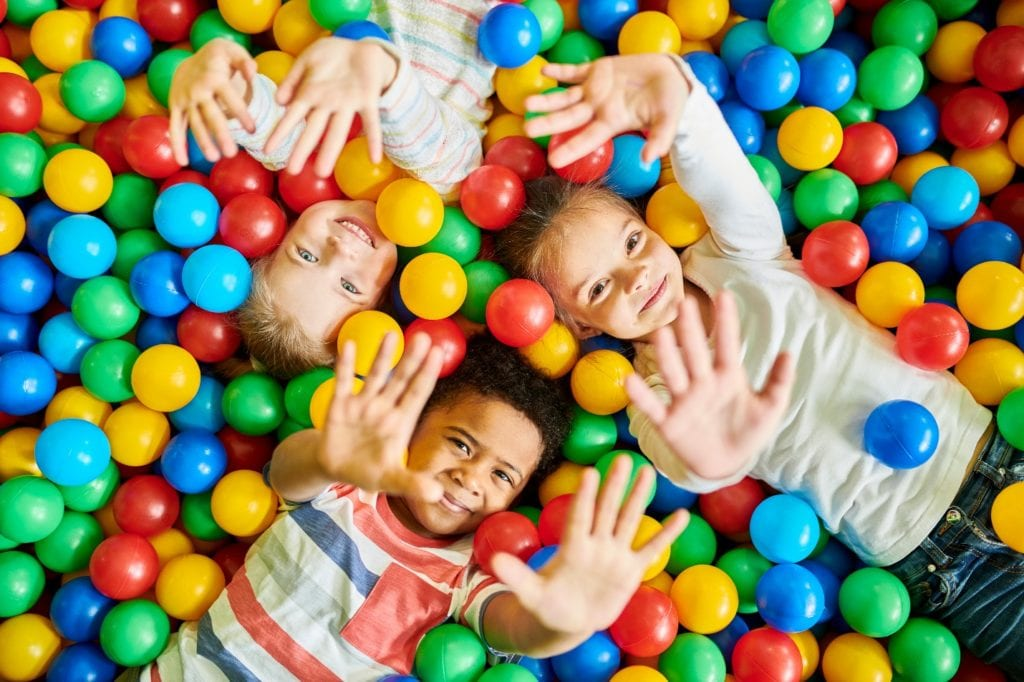 three happy little kids in ball pit smiling at camera raising hands